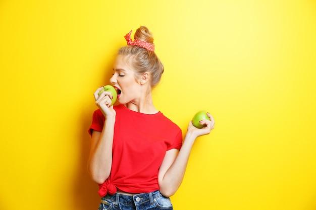 Молодая красивая женщина с яблоками на желтой поверхности