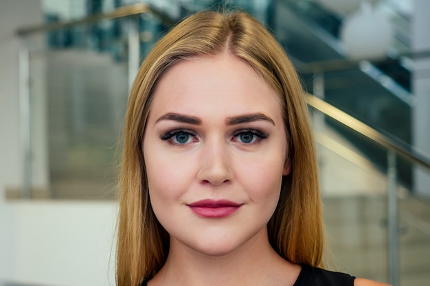 Young and beautiful woman with artificial extended silk eyelashes eyes opened in a beauty studio, close up perfect skin