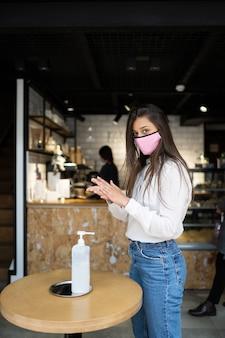 手消毒剤ジェルを使用して手を洗う防護マスクで魅力的な笑顔を持つ若い美しい女性。女の子はカフェシーンで外のしきい値を立っています。コロナウイルス予防のコンセプト。