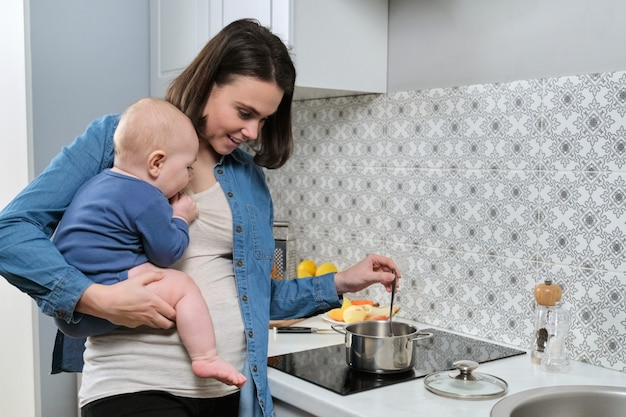 Young beautiful woman with baby in her arms in kitchen