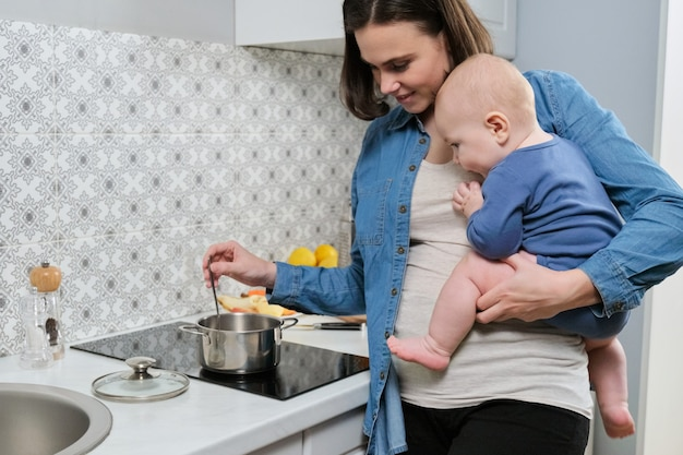 Молодая красивая женщина с ребенком на руках на кухне