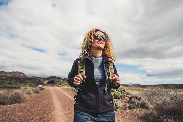 山でハイキングバックパックとトレッキング服を着た若い美しい女性。健康的でアクティブなライフスタイルをコンセプトに。