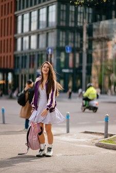 カメラでポーズをとってバックパックを持つ若い美しい女性