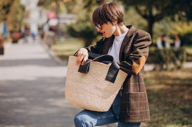 通りの外でバッグを持つ若い美しい女性