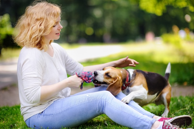 Young beautiful woman with beagle dog in the summer park. loving female owner with her domestic pet