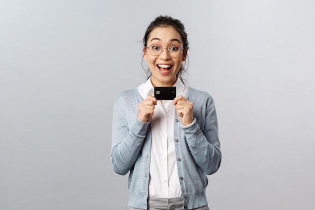 黒のクレジットカードを持つ若い美しい女性