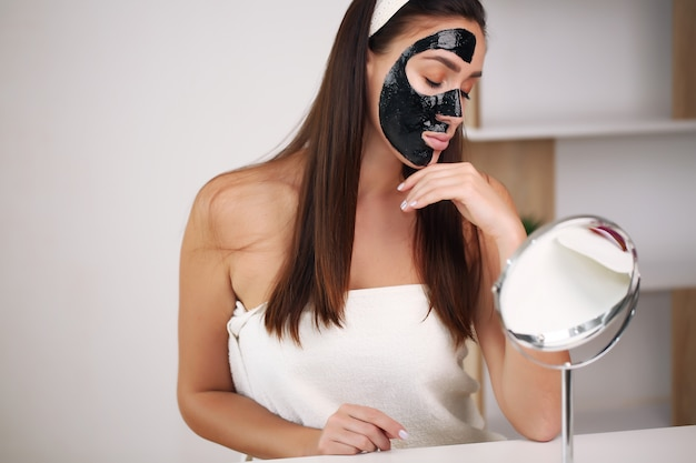 Young and beautiful woman with black peel-off mask on her face after shower