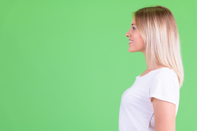 Young beautiful woman with blond hair against chroma key on green