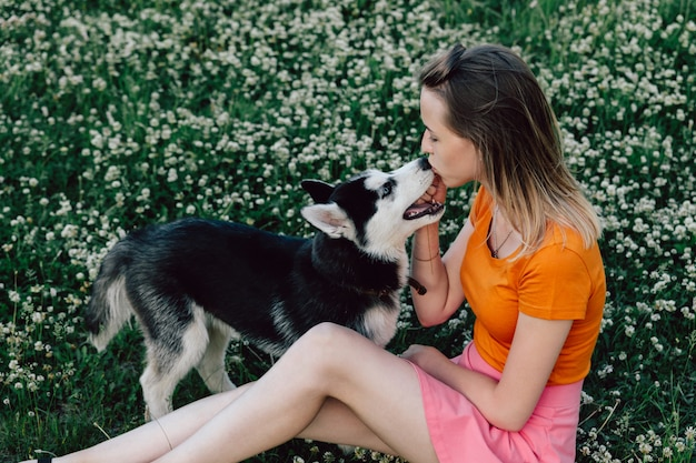 A young beautiful woman with blond hair is sitting in the meadow with her pet puppy husky and kissing him on the nose.