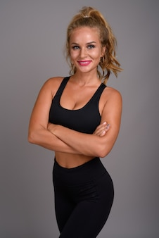 Young beautiful woman with blond hair ready for gym against gray