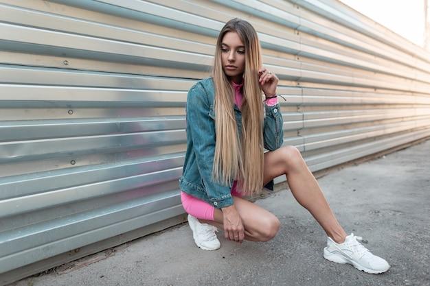 흰색 유행 운동화에 여름 세련된 데님 옷에 금발 긴 머리를 가진 젊은 아름 다운 여자는 여름 화창한 날에 금속 벽 근처 도시에 앉아있다. 야외에서 휴식하는 현대 소녀. 레트로 스타일.