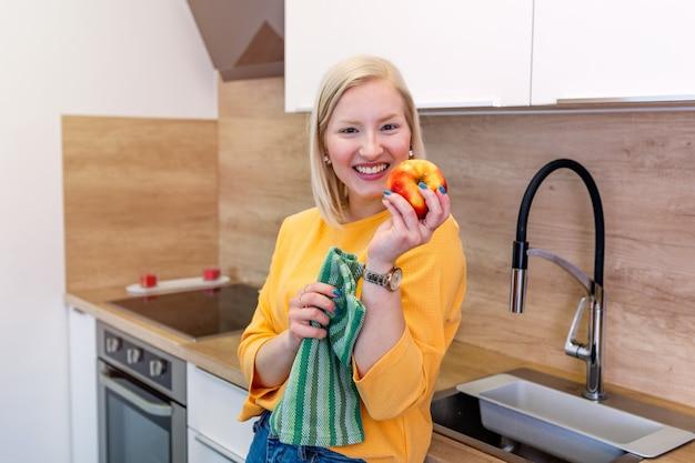 彼女の自宅の台所に立っている間ジューシーな赤いリンゴを食べてブロンドの赤い髪の若い美しい女性。果物とビタミンの毎日の摂取