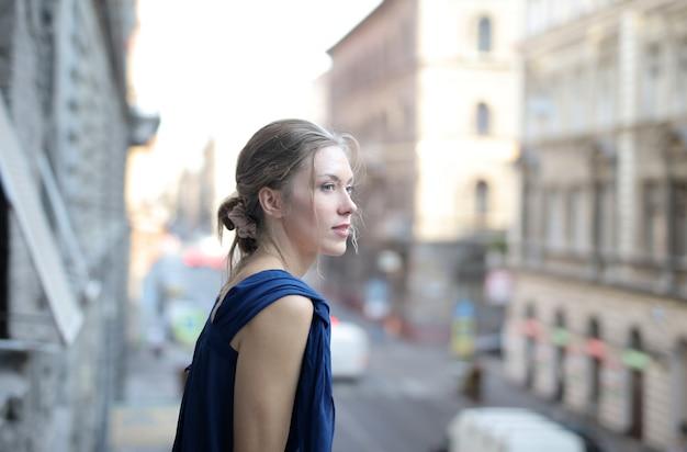 흐리게 거리 거리와 금발 머리를 가진 젊은 아름 다운 여자