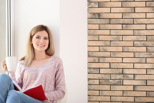 窓枠に座っている本と飲み物のカップを持つ若い美しい女性。