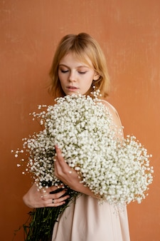 Young beautiful woman with bouquet of delicate spring flowers