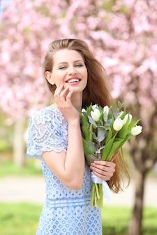 春の公園でチューリップの花束を持つ若い美しい女性 Premium写真
