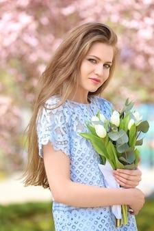 봄 공원에서 튤립 꽃다발을 든 아름다운 젊은 여성