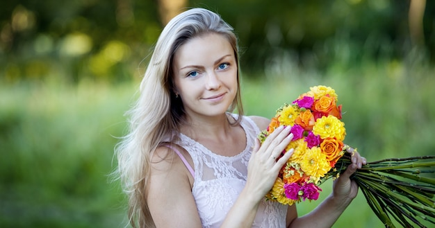 Young beautiful woman with a bright bouquet of flowers, outdoors, warm sunny day