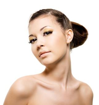 明るい黄色の化粧と茶色の髪の若い美しい女性。