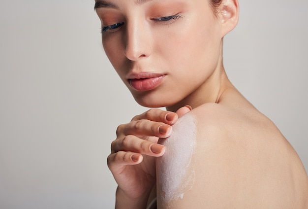 A young beautiful woman with brown hair and clean skin smears a moisturizer on the shoulder. moisturizing and body care.