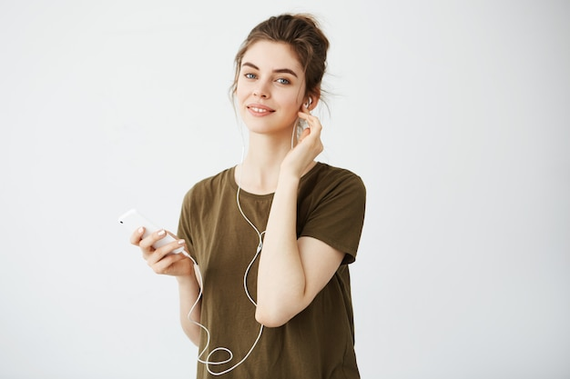 Young beautiful woman with bun smiling listening music in headphones over white background.