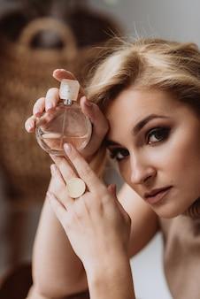 깨끗한 피부를 가진 젊고 아름다운 여성은 손에 향수 한 병을 들고 카메라를 쳐다봅니다. 클로즈업 초상화입니다. 부드러운 선택적 초점입니다.