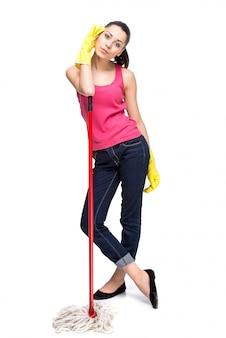 掃除ほうきを持つ若い美しい女性。
