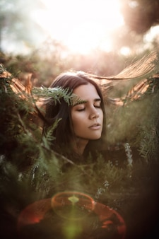 Young beautiful woman with closed eyes in a isolated bush looking right with back light and flares