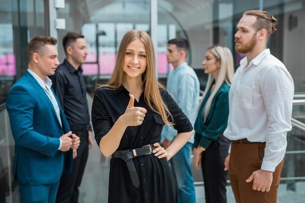 Молодая красивая женщина с коллегами в офисе с жестом руки