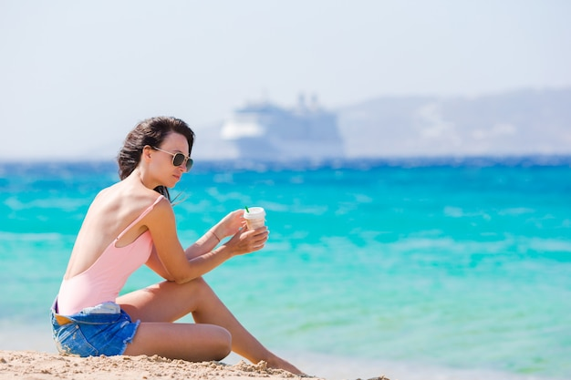 熱帯の休暇中にビーチでコーヒーを飲みながら若い美しい女性。女の子は、ミコノス島、ギリシャ、ヨーロッパの美しいビーチの1つで彼女の週末をお楽しみください。