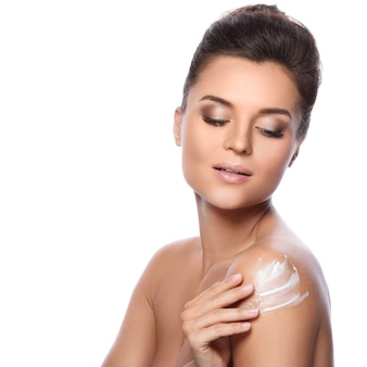 Young beautiful woman with cream on her shoulder
