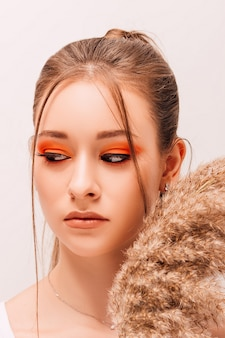 Young beautiful woman with creative makeup and dried flowers