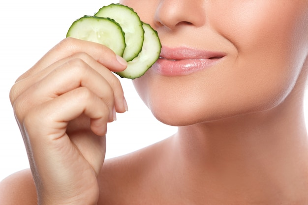 Young beautiful woman with cucumber slices