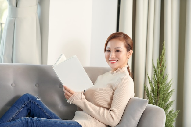 Young beautiful woman with cup of tea sitting home in living room by the window reading book.