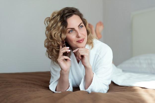 Молодая красивая женщина с вьющимися распущенными волосами лежит на кровати в номере отеля, одетая в белый махровый халат, разговаривает по телефону и смотрит в сторону с легкой улыбкой на лице