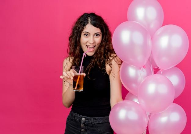 Giovane bella donna con capelli ricci che tiene mazzo di mongolfiere e cocktail sorridente allegramente in piedi sopra il muro rosa