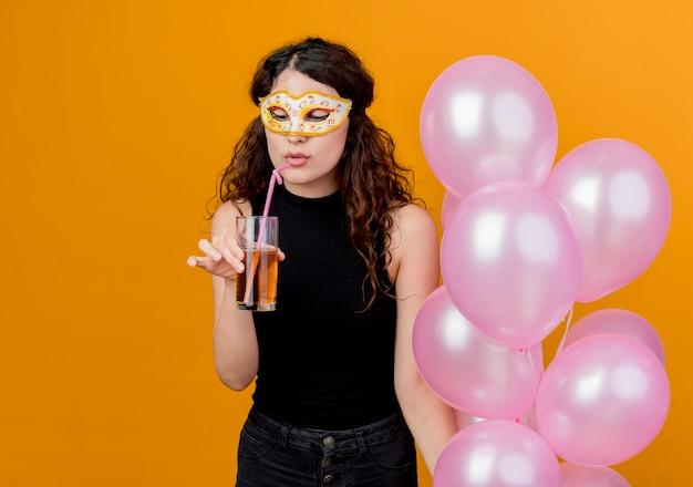 Giovane bella donna con capelli ricci che tiene mazzo di mongolfiere nella maschera del partito felice e allegro concetto di bere cocktail festa di compleanno in piedi sopra la parete arancione