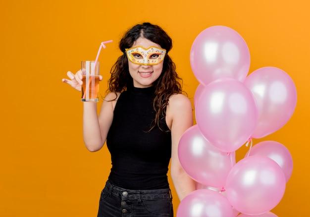 Giovane bella donna con capelli ricci che tiene mazzo di mongolfiere nella maschera di partito felice e allegro bere cocktail festa di compleanno concetto in piedi sopra la parete arancione