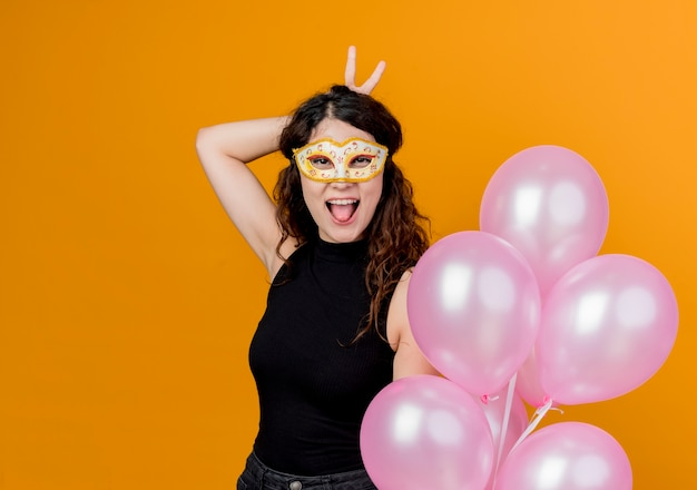 Young beautiful woman with curly hair holding bunch of air balloons in party mask happy and cheerful sticking out tongue birthday party concept over orange
