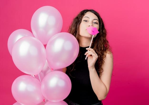 Giovane bella donna con capelli ricci che tiene mazzo di palloncini d'aria e bastone da festa sorridente allegramente in piedi sopra il muro rosa