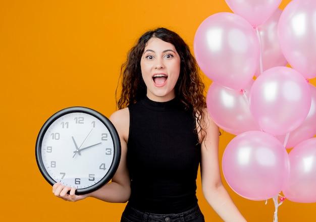 Giovane bella donna con capelli ricci che tiene mazzo di mongolfiere e orologio da parete concetto di festa di compleanno felice ed eccitato in piedi sopra la parete arancione