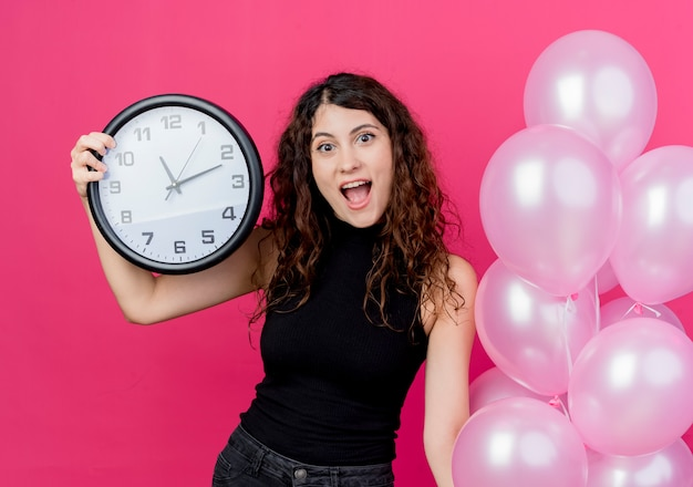 Young beautiful woman with curly hair holding bunch of air balloons and wall clock smiling cheerfully standing over pink wall