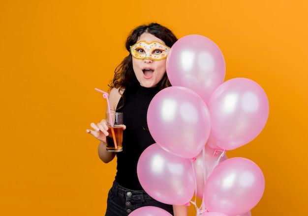 오렌지를 통해 파티 마스크 행복하고 쾌활한 생일 파티 개념에 공기 풍선의 무리와 칵테일을 들고 곱슬 머리를 가진 젊은 아름 다운 여자