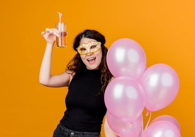 오렌지 벽 위에 서 파티 마스크 행복하고 쾌활한 생일 파티 개념에 공기 풍선의 무리와 칵테일을 들고 곱슬 머리를 가진 젊은 아름 다운 여자