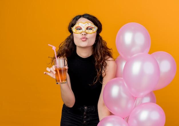 오렌지 벽에 키스 생일 파티 개념 서를 불고 행복하고 쾌활한 파티 마스크에 공기 풍선의 무리와 칵테일을 들고 곱슬 머리를 가진 젊은 아름 다운 여자