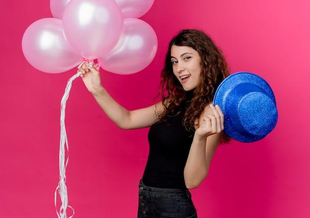 분홍색 벽 위에 유쾌하게 서 웃고 공기 풍선과 휴가 모자의 무리를 들고 곱슬 머리를 가진 젊은 아름 다운 여자