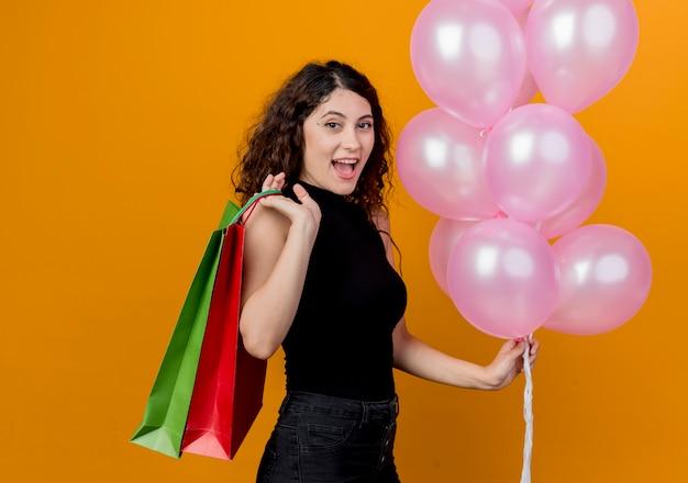 オレンジ色の壁の上に立っている気球と紙袋の束を保持している巻き毛の若い美しい女性幸せで陽気な笑顔の誕生日パーティーのコンセプト