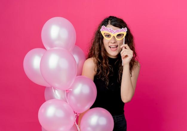 분홍색 벽 위에 유쾌 하 게 서 웃 고 공기 풍선 및 종이 안경의 무리를 들고 곱슬 머리를 가진 젊은 아름 다운 여자