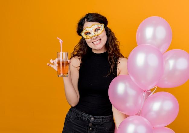 오렌지 벽 위에 서 파티 마스크 행복하고 쾌활한 칵테일 생일 파티 개념 서에서 공기 풍선의 무리를 들고 곱슬 머리를 가진 젊은 아름 다운 여자
