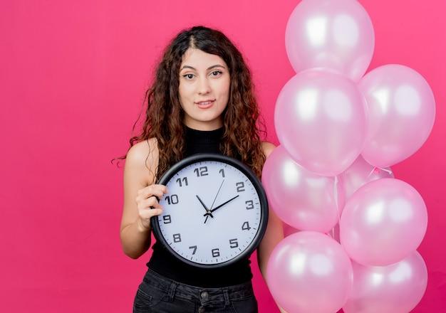 분홍색 벽 위에 유쾌하게 서 웃고 공기 풍선 벽 시계의 무리를 들고 곱슬 머리를 가진 젊은 아름 다운 여자